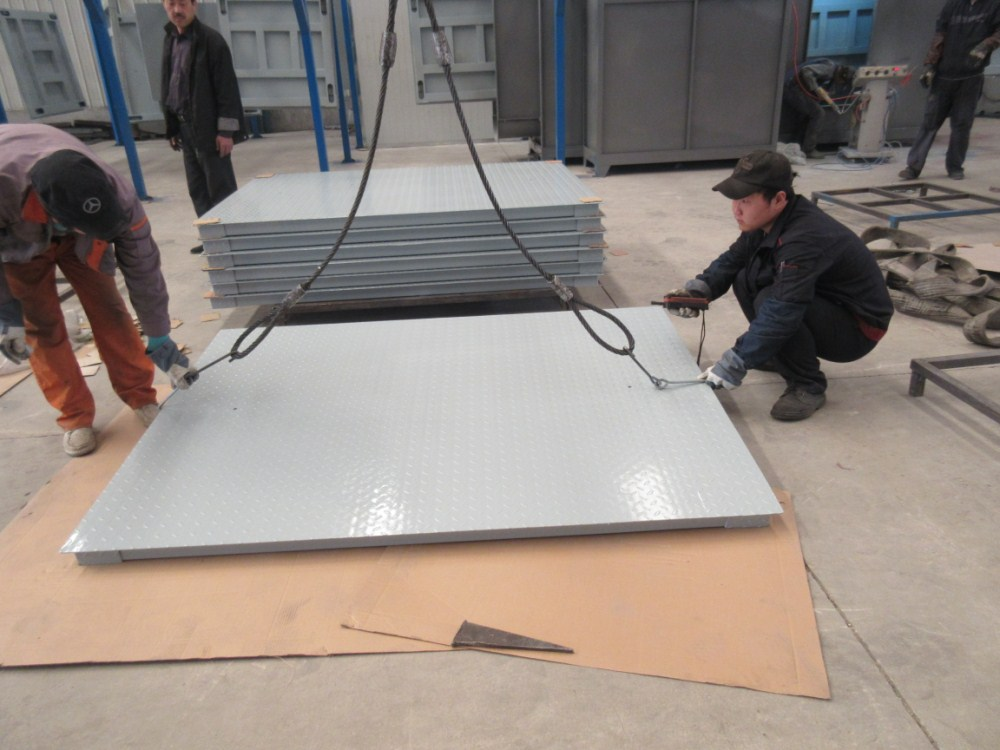 two men hooking a metal sheet to a lifting equipment