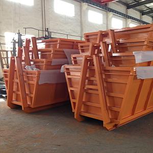 a stack of orange hooklift bins